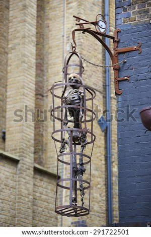LONDON, UK - JUNE 23: Replica of skeleton in cage at the entrance to The Clink prison museum, which exhibits medieval torture tools. June 23, 2015 in London. - stock photo