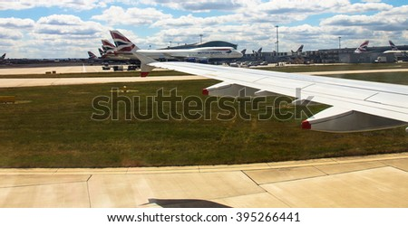 LONDON, UK - JUNE 03, 2015: Taxiing aircraft Airbus A-320  after landing  in Heathrow Airport near British Airway passenger jet airplane  Boeing 747-400 on cloudy sky background - stock photo