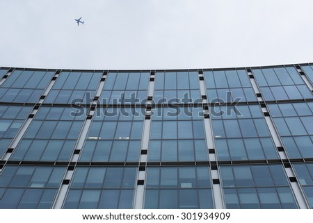 LONDON, UK - JUNE 20, 2015 - Top of a building in London as a commuter aircraft flies past overhead
