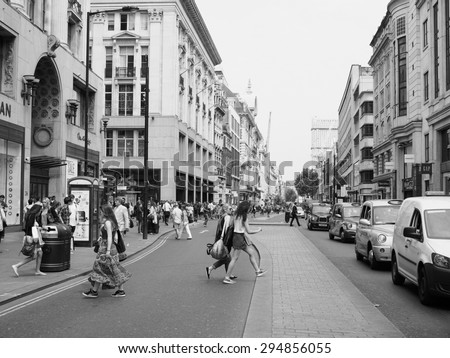 LONDON, UK - JUNE 12, 2015: Tourists in busy central London street in black and white - stock photo
