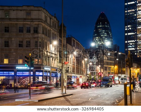 LONDON, UK - JUNE 17, 2015: Traffic and Gherkin building in the background at night. The Gherkin has become an iconic symbol of London.