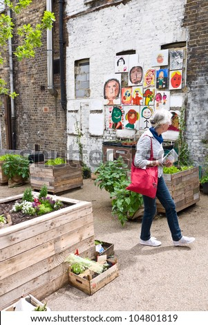LONDON, UK-JUNE 9: Visitors enjoying a peaceful  haven in a secret garden, Dalston Eastern Curve with street art  among the planting.Part of the Open Garden Squares Weekend. June 9, 2012 in London UK - stock photo