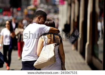 London, UK - June 3, 2013: Young couple in love, hugging on the street.  - stock photo