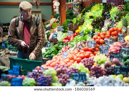 LONDON, UK - MAR 22: An unidentified man purchases fruits and vegetables at a stall in Borough Market in London on March 22, 2014.  - stock photo