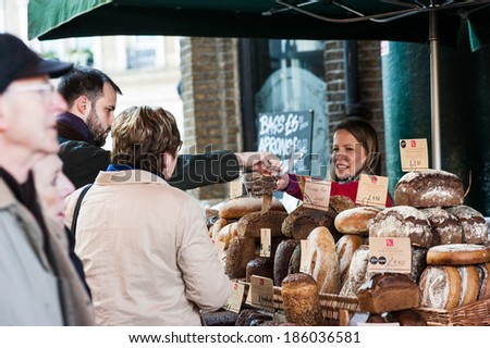 LONDON, UK - MAR 22: Unidentified people purchase bread at a bakery in Borough Market in London on March 22, 2014.  - stock photo