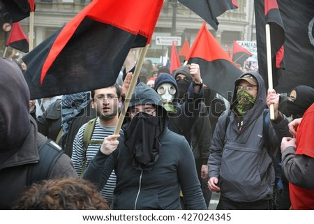 London, UK - March 26, 2011: A breakaway group of anarchist protesters march through the streets of the British capital during a large anti cuts rally. - stock photo