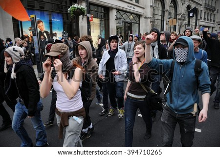 London, UK - March 26, 2011: A breakaway group of protesters some wearing masks march through the streets of the British capital during a large anti cuts rally. - stock photo