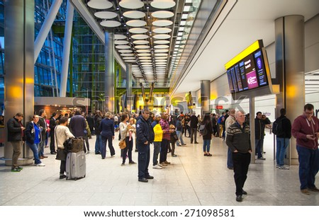 LONDON, UK - MARCH 28, 2015: People waiting for arrivals in Heathrow airport Terminal 5 - stock photo