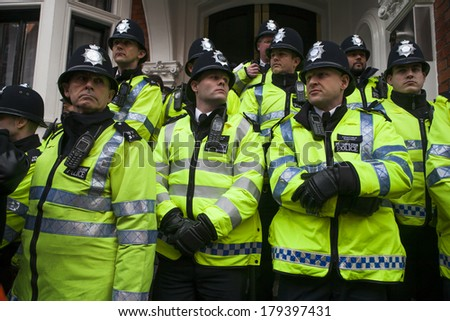 LONDON, UK - MARCH 1TH 2014. London protesters march against worldwide government corruption..Police watch  In London on 1th March 2014. - stock photo