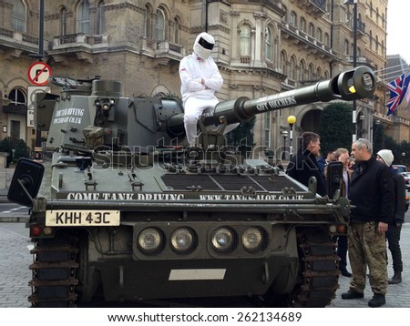 LONDON, UK - MARCH 20, 2015:  The Stig on a tank at  BBC Broadcasting House after delivering a petition supporting Jeremy Clarkson. The Top Gear presenter is suspended after a fracas with a producer.  - stock photo