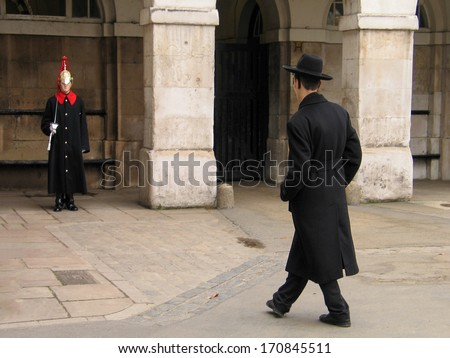 LONDON, UK - MARCH 30, 2006: Two young people - member of the Household Cavalry on duty and jewish orthodox visitor have met in London, UK on March 30, 2006. London is the world's most-visited city  - stock photo