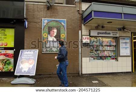 LONDON, UK - MAY 24, 2014:  A pedestrian looks at the memorial to Jean Charles de Menezes the innocent tube traveller killed by police after July 7th 2005 bomb attacks.  Stockwell Tube Station.