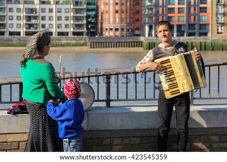 London, UK - May 10, 2015 - Immigrant busker playing accordion alongside his family on London's South Bank - stock photo