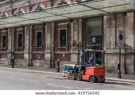 LONDON, UK - MAY 12, 2016:  Man drives a forklift truck outside Smithfileds Market in Farringdon area