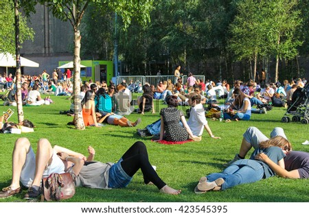 London, UK - May 10, 2015 - People sitting and relaxing on the green grass in front of Tate Modern on London's South Bank