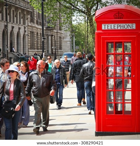 LONDON, UK - MAY 13, 2012: People walk past telephone booth in London. With more than 14 million international arrivals in 2009, London is the most visited city in the world (Euromonitor). - stock photo