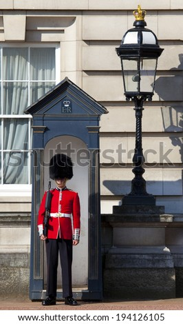 LONDON, UK - MAY 16TH 2014: A Queen's Guard outside the historic Buckingham Palace in London on 16th May 2014. - stock photo