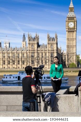 LONDON, UK - MAY 14, 2014  - Young TV team shooting the news on the Big Ben and Parliament background - stock photo
