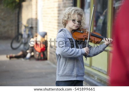 LONDON, UK-NOVEMBER 16: children play the violin at the Christmas Fair. Broadway market. November 16, 2016 in London UK