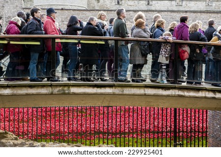 LONDON, UK - NOVEMBER 08: People queueing to see red poppies art installation at Tower of London. November 08, 2014 in London. The ceramic poppies were planted to mark the centenary of WWI's outbreak. - stock photo