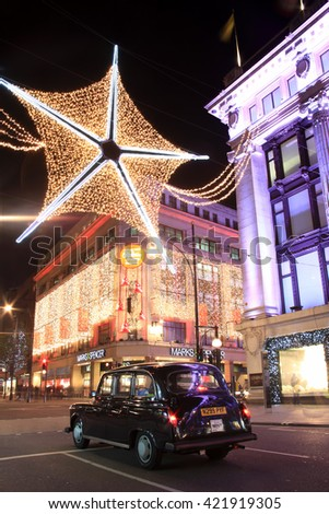 London, UK - November 10, 2011: The Christmas lights decorations outside Marks & Spencer and Selfridges at night in Oxford Street, during the festive season, with a black taxi cab in the foreground. - stock photo