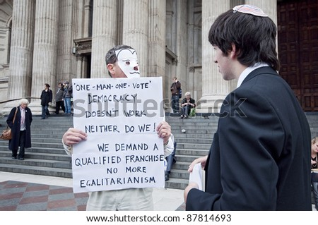 LONDON, UK -OCTOBER 31: A Jewish school boy listening to one of the protesters with banner outside St. Paul's Cathedral on 31, 2011 in London.