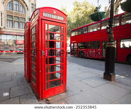 LONDON, UK - OCTOBER 7, 2014:  London England street scene featuring iconic red phone box and double-deck bus in background.  - stock photo