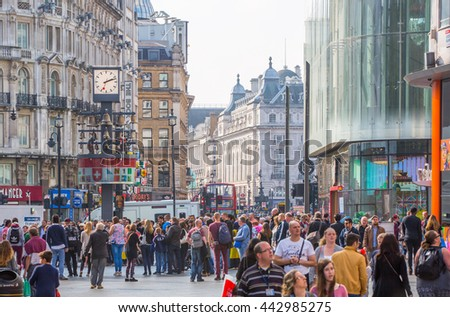LONDON, UK - OCTOBER 4, 2015:Lots of people, tourists and Londoners walking via Leicester square, the famous destination of London for night life, cinemas, restaurants and bars - stock photo