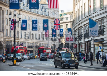 LONDON, UK - OCTOBER 4, 2015: Regent street decorated with flags and lots of walking people. Public transport on the road, taxis, cars and buses