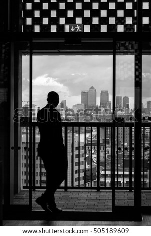 LONDON, UK - OCTOBER 20, 2016: Silhouetted man enjoys high angle view of London skyline from the viewing gallery in the new Tate Modern extension