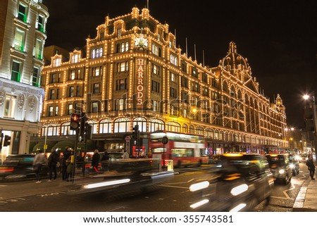LONDON, UK - 23RD DECEMBER 2015: The outside of Harrods Department Store in London at night during the Christmas Season. People and traffic can be seen. - stock photo