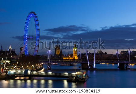 LONDON, UK - 23RD MARCH 2014: Cityscape of London at night with the London Eye, Houses of Parliament and Hungerford Bridge - stock photo