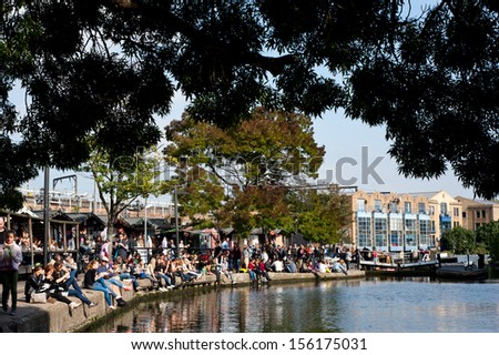 LONDON, UK - SEPT 29: people enjoy the sunshine on the Regent's Canal in London on September 29, 2013. The Canal, 8.6 miles, links Paddington to the Limehouse Basin and the River Thames in east London. - stock photo
