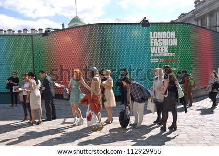 LONDON, UK-SEPTEMBER 14: Fashionable visitors que for the cat walk shows at the internationally famous London'Fashion Week at Somerset House. September 14, 2012 in London UK - stock photo