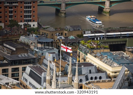 LONDON, UK - SEPTEMBER 17, 2015: Flag of England on the cathedral tower,  with River Thames and London bridge