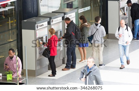 LONDON, UK - SEPTEMBER 12, 2015: People purchasing train tickets from machine. Liverpool street train station with lots of people - stock photo