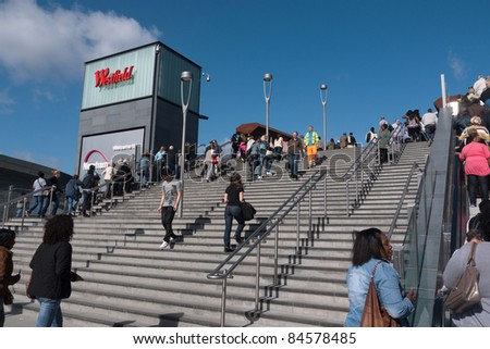 LONDON, UK- SEPTEMBER 13: Shoppers on the steps to the opening of Westfield Stratford City, the largest urban shopping centre in Europe, and gateway to the Olympic Park. September 13, 2011 London UK - stock photo