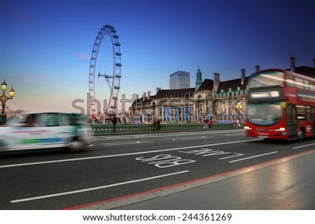 LONDON, UK - September 17, 2014: Traffic on Westminster bridge on September 17, 2014 in London. Traditional London public transportation on the London Eye  background at night. - stock photo