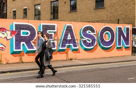 "London, UK - 19 September 2015: Two girls walking in front of a big graffiti with the word ""Reason"" written on it. Shot in Shoreditch an area of London popular among young trendy people. - stock photo"