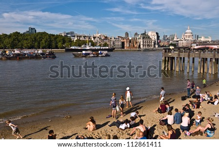 LONDON, UK-SEPTEMBER 8: Visitors enjoy the sun and temporary urban beach along the foreshore of the Thames at Gabriels wharf, St Pauls Cathedral is in the background.September 8, 2012 in London UK. - stock photo