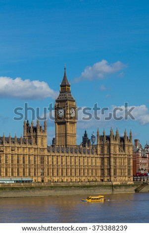 LONDON, UK - 18TH JULY 2015: Elizabeth Tower/Big Ben and part of the Palace of Westminster during the summer. A Duck Tours boat can be seen in the Thames