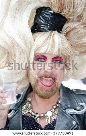 London, UK. 27th June 2015. EDITORIAL - A very joyful participant at the Pride In London 2015 parade, the bearded man is wearing a large blonde wig and make-up. Photo taken near Trafalgar Square.