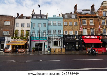 LONDON, UK - 26TH MARCH 2015:  A view of various restaurants and businesses along Upper Street in Islington, london. People can be seen. - stock photo