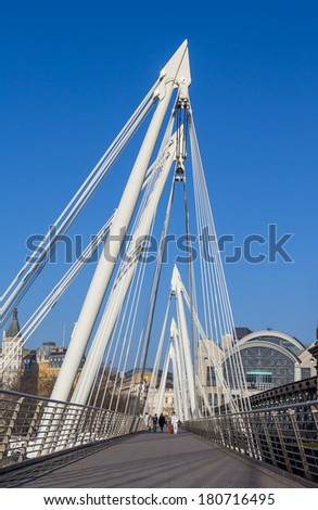LONDON, UK - 9TH MARCH 2014: The Hungerford Bridge in London with people walking across it during the day