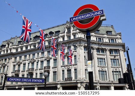 LONDON, UK - 24TH MAY 2012: London Underground sign and Union Flags at Oxford Circus station. - stock photo