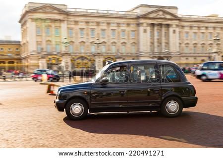 LONDON, UK - 26TH SEPTEMBER 2014: A Black Cab moving along the road outside Buckingham Palace - stock photo