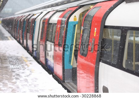 London underground train in the snow waiting for people to board - stock photo