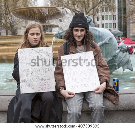 London, United Kingdom - April 16, 2016: Anti-Austerity March. Two homemade signs, one quoting George Osbourne hypocritical stand on tax evasion and the other a comment on David Cameron's old school.