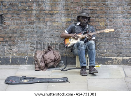 London, United Kingdom - April 30, 2016:Busking on Brick Lane. Brick Lane is area of diversity. It is very popular tourist destination with many ethnic eating places and markets and people busking. - stock photo