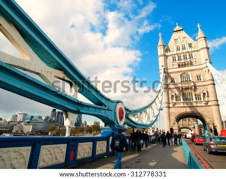 London, United Kingdom - April 30, 2008 : Cars and pedestrians crossing River Thames on Tower Bridge during the day - stock photo